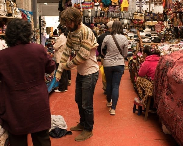 man tries on a sweater in outdoor market Peru
